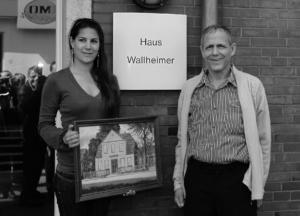 Berni Wallheimers Sohn Nir mit Tochter Adina in Aurich vor dem Haus am Breiten Weg 1. Adina hält ein Bild vom Haus.