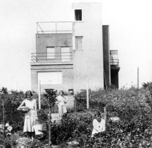 Die Fotografie aus dem Jahr 1930 zeigt drei in luftigem Weiß gekleidete Frauen inmitten eines üppigen sommerlichen Gartens. Die beiden jungen Frauen im Vordergrund blicken von der Ernte auf und lächeln in die Kamera. Hinter ihnen führen Treppen einen kleinen Hügel hinauf, hin zu einem Haus mit klaren und einfachen Linien. Auf einer dieser Treppen steht die Malerin Lucy Ortlepp, selbstbewusst und entspannt blickt sie dem Fotografen entgegen – es ist ihr neues Zuhause, vor dem sie zu sehen ist. Das Haus befindet sich am Weimarer Ratstannenweg 21. Noch heute ist das Namensschild der Ortlepps an seiner Eingangspforte angebracht – in Erinnerung an die früheren Besitzer.